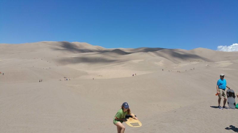 girl climbing dunes with sand board