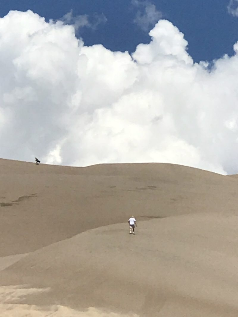 man walking up sand dune