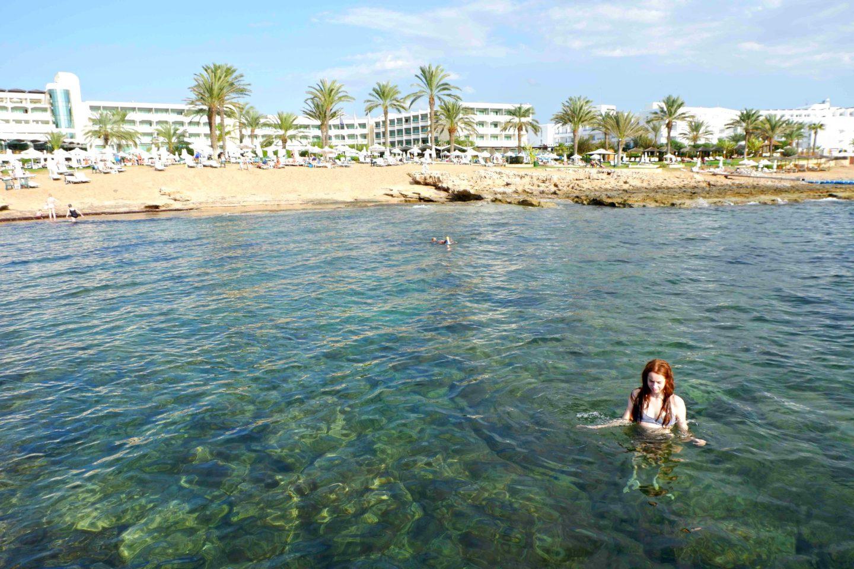 girl in Ocean in front of Athena Beach Hotel